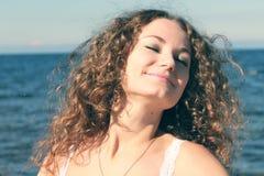 Schöner junger Brunette, der durch das Meer sich entspannt Lizenzfreie Stockfotografie