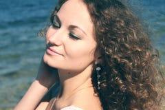 Schöner junger Brunette, der durch das Meer sich entspannt Stockbilder