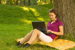 Schöner junger Brunette, der an einem Laptop im Park arbeitet Lizenzfreie Stockfotografie