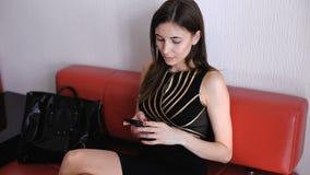 Schöner junger Brunette, der einen Smartphone verwendet stock video