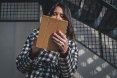 Schöner junger Brunette, der ihre Tablette in den Stadtstraßen verwendet Stockbilder
