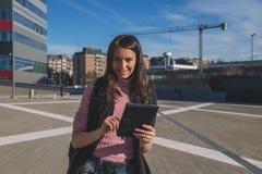Schöner junger Brunette, der an ihrer Tablette arbeitet Stockfoto