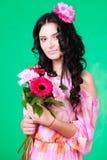 Schöner junger Brunette in einem rosa Kleid mit einem Bündel von Gerbera Stockfoto