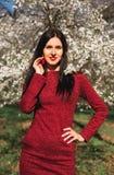 Schöner junger Brunette mit dem langen Haar in einem Park auf einem Frühling mitten in blühenden Bäumen in einem roten Kleid Lizenzfreie Stockbilder