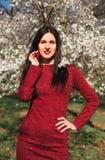 Schöner junger Brunette mit dem langen Haar in einem Park auf einem Frühling mitten in blühenden Bäumen in einem roten Kleid Lizenzfreies Stockbild