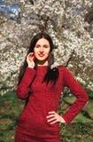 Schöner junger Brunette mit dem langen Haar in einem Park auf einem Frühling mitten in blühenden Bäumen in einem roten Kleid Lizenzfreie Stockfotografie