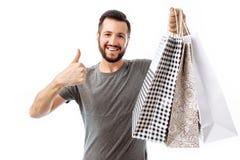Schöner junger Hippie, Shopaholic mit Taschen zeigt Klasse isola lizenzfreies stockfoto
