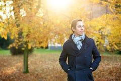 Schöner junger Mann, der draußen an einem Herbsttag aufwirft Lizenzfreies Stockbild