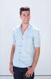 Schöner junger Mann, der draußen gegen weißen Hintergrund lächelt Lizenzfreies Stockbild