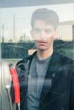 Schöner junger Mann, der in einer Telefonzelle aufwirft Lizenzfreie Stockfotos