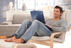 Schöner junger Mann, der sich zu Hause mit Laptop entspannt