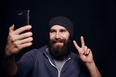 Schöner junger Mann mit einem Bart macht Selbst Stockfotos