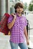Schöner junger Mann nach dem Einkauf Stockbild