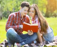Schöner junger Mann und Mädchen des Porträts, die ein Buch liest Stockbild