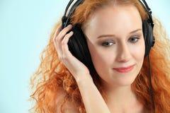 Schöner junger Redhead mit Kopfhörern Stockfotografie