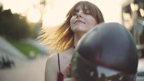 Schöner junger rothaariger Frauenmotorradfahrer entfernt Sturzhelm auf Sonnenuntergang stock footage