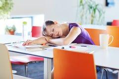 Schöner junger Student, der in der Bibliothek oder im Klassenzimmer studiert Lizenzfreie Stockfotografie