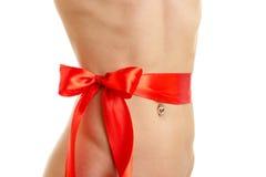 Schöner junges Mädchen ` s Bauch mit einem roten Band ist auf einem weißen Hintergrund Stockbilder