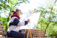 Schöner Künstler zeichnet ein Bild in einer guten Laune draußen lizenzfreies stockbild