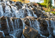Schöner künstlicher Wasserfall am Vorfrühlingsmorgen Lizenzfreies Stockbild