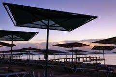 Schöner Küstesonnenaufgang mit Strandregenschirmen Lizenzfreie Stockfotos