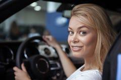 Schöner Kaufenneuwagen der jungen Frau an der Verkaufsstelle stockfoto