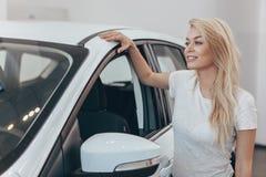 Schöner Kaufenneuwagen der jungen Frau an der Verkaufsstelle lizenzfreies stockbild
