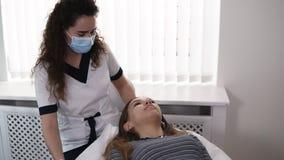 Schöner kaukasischer Cosmetologist lädt den Kunden ein, auf der Couch niederzulegen und examinating die Mädchenbrauen stock video