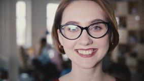 Schöner kaukasischer weiblicher Führer, der an der Kameranahaufnahme lächelt Porträt des glücklichen Frauenmanagers in den Gläser stock video