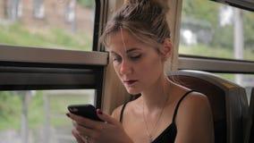 Schöner kaukasischer weiblicher Tourist sitzt im Zug an der Station Benutzt Drucke eines Handys eine Mitteilung und ein traurig l stock video footage