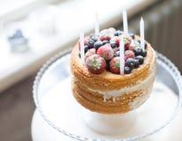Schöner Kekskuchen mit der weißen Creme verziert mit den Erdbeerblaubeeren und weißen Kerzen, die auf dem Stand am Gewinn stehen Lizenzfreie Stockbilder