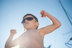 Schöner kleiner Junge in der Sonnenbrille, die seinen Muskel im sonnigen Tag des Sommers zeigt Lizenzfreies Stockfoto