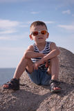 Schöner kleiner Junge in der Sonnenbrille eine Weste und kurze Hosen, die auf einem Hintergrund des Himmels und des Meeres sitzen Stockbild