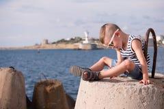 Schöner kleiner Junge in der Sonnenbrille sitzt auf dem Hintergrund des Meeres Stockfotografie