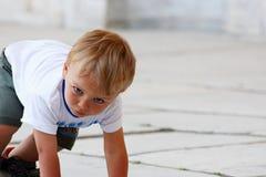 Schöner kleiner Junge des blonden Haares bereit zu laufen Stockfotografie