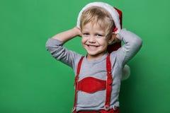 Schöner kleiner Junge kleidete wie das Santa Claus-Helferlächeln an Weihnachtsniederlassung und -glocken Stockfotografie