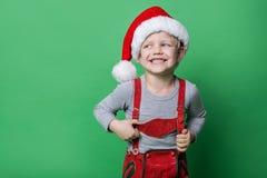 Schöner kleiner Junge kleidete wie Weihnachtselfe mit großem Lächeln an Weihnachtsniederlassung und -glocken Lizenzfreies Stockbild