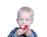 Schöner kleiner Junge mit dem blonden Haar und den blauen Augen hält Stockbild