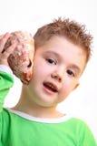 Schöner kleiner Junge mit einem Shell vom Meer Lizenzfreie Stockbilder