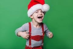 Schöner kleiner Junge mit Santa Claus-Hutlachen Weihnachtsniederlassung und -glocken Lizenzfreie Stockfotos
