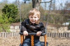 Schöner Kleinkindjunge, der Spaß auf Schwingen hat Lizenzfreies Stockfoto