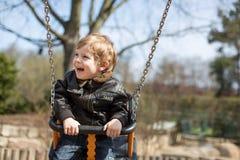 Schöner Kleinkindjunge, der Spaß auf Schwingen hat Lizenzfreie Stockbilder