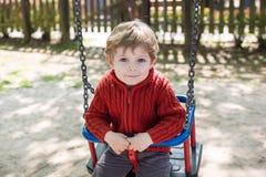 Schöner Kleinkindjunge, der Spaß auf Schwingen hat Stockfoto