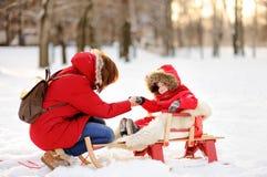 Schöner Kleinkindjunge und seine Mutter, die Spaß im Winter hat Stockfoto
