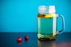 Schöner Kräutertee mit Zitrone an der Glasflasche lizenzfreies stockbild