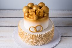 Schöner Kuchen für den 50. Jahrestag der Hochzeit verziert mit Goldkugeln und Ringen Konzept von festlichen Nachtischen Stockfotos