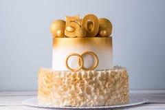 Schöner Kuchen für den 50. Jahrestag der Hochzeit verziert mit Goldkugeln und Ringen Konzept von festlichen Nachtischen Stockbilder