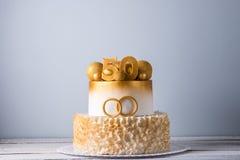 Schöner Kuchen für den 50. Jahrestag der Hochzeit verziert mit Goldkugeln und Ringen Konzept von festlichen Nachtischen Stockfoto