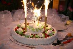 Schöner Kuchen für die Heirat mit Zahlen von Schwänen und von brennendem fla Lizenzfreies Stockbild