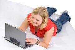 Schöner Kursteilnehmer, der auf Bett studiert Stockbilder